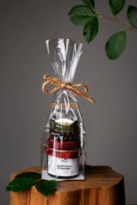 Słoiczek dżemu, ozdobiony materiałowym kapturkiem, na którym stoi opakowanie aronii w czekoladzie. Całość opakowana w celofanową torebkę. Przewiązana jutowym sznurkiem.